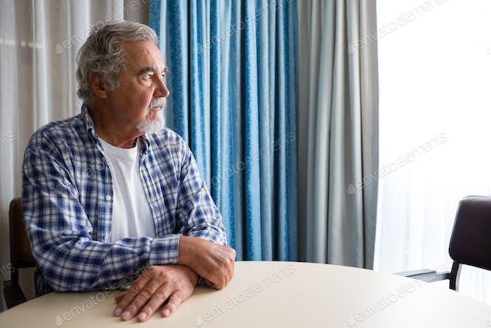 Thoughtful senior man sitting at table in nursing home