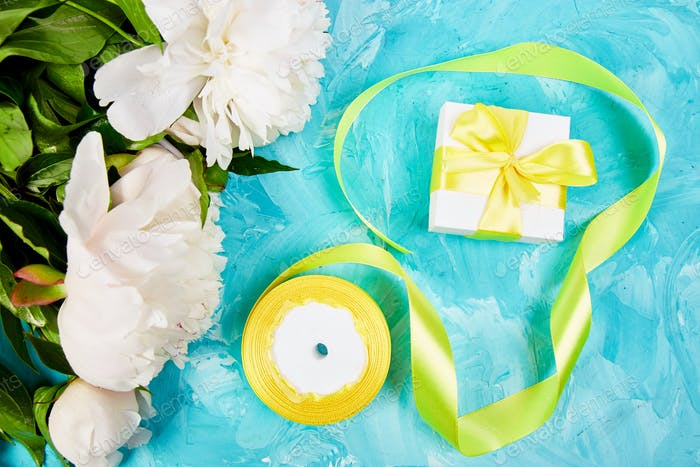 Wrapping white gift with yellow ribbon, white flower peony