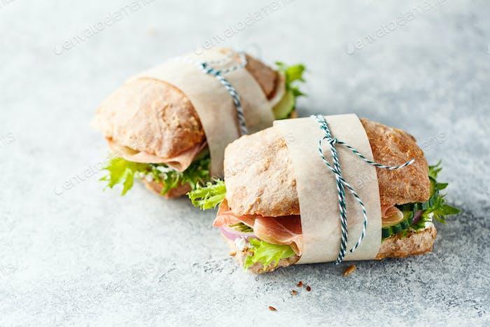 Zwei frische Sandwiches mit Schinken, Gurken, Salat und Zwiebeln