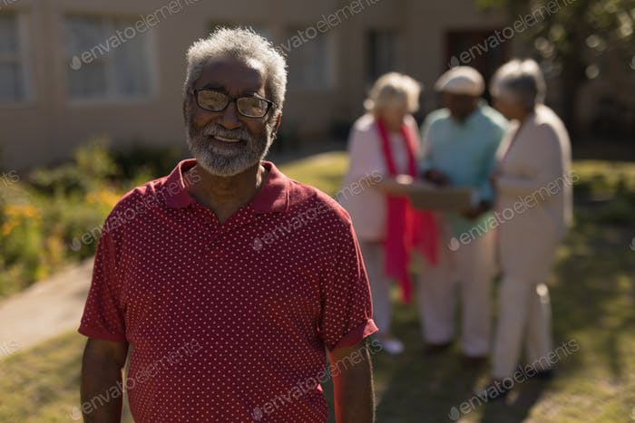 Portrait of happy African-American senior man standing in park