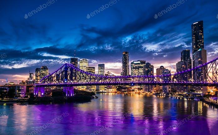 Vibrante panorama Noche de la Ciudad de Brisbane con luces moradas