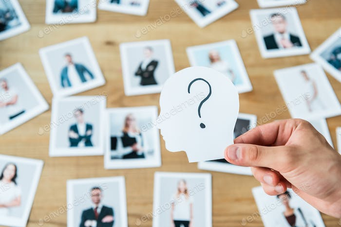 cropped view of man holding paper with human head and question mark near photos