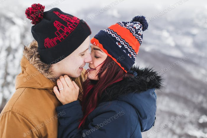 Tender portrait of young kissing couple. Winter look