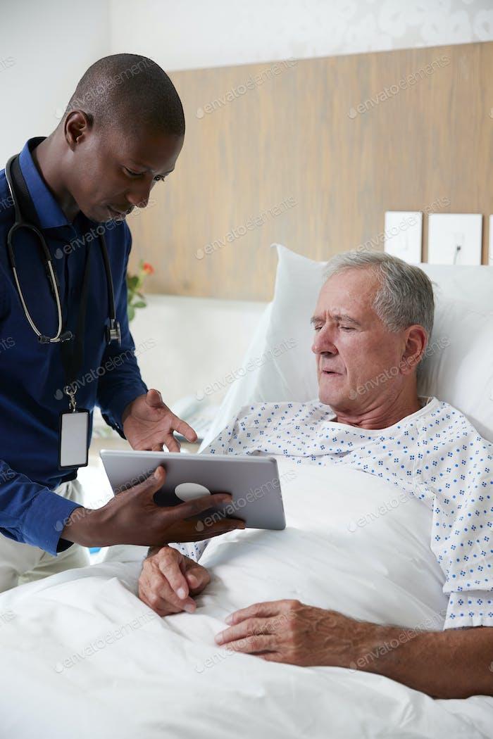 Arzt mit Digital-Tablette Besuch und Gespräch mit Senior männlichen Patienten im Krankenhaus Bett