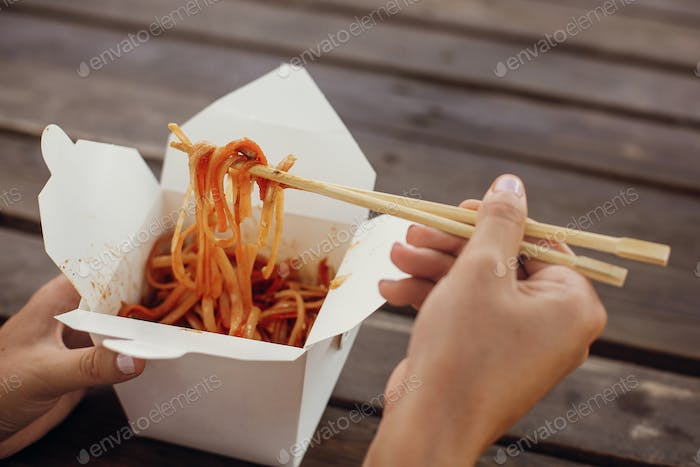 Wok with noodles and vegetables in carton box to go and bamboo chopsticks