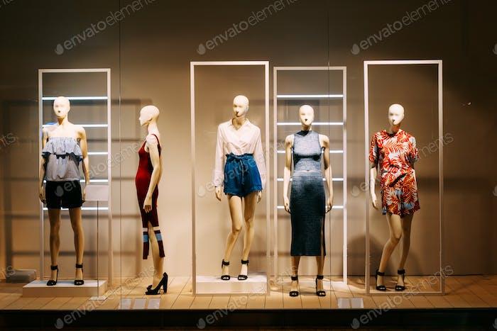 Five Mannequins Standing In Store Window Display Of Women's Casu