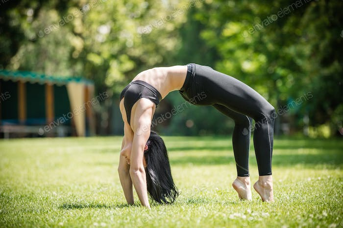 Young woman performing bridge exercise in park