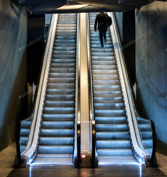Man ascending an escalator from a subway