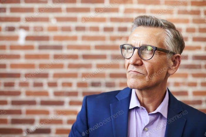 зрелые бизнесмен стоя против кирпичной стены в современный офис