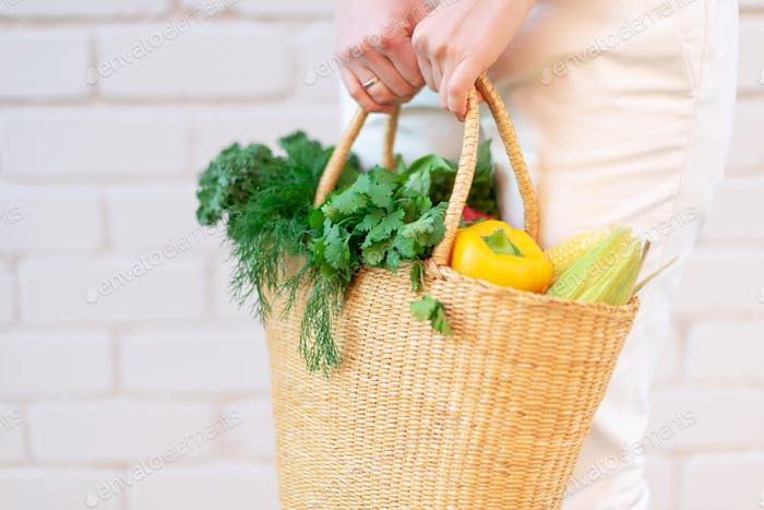 Thumbnail for Zero waste concept with copy space. Woman holding straw basket with vegetables, products. Eco