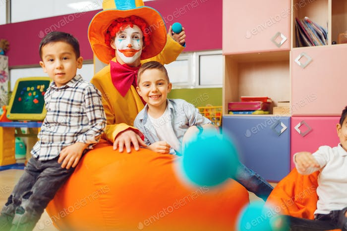 Funny clown with little boy in kindergarten