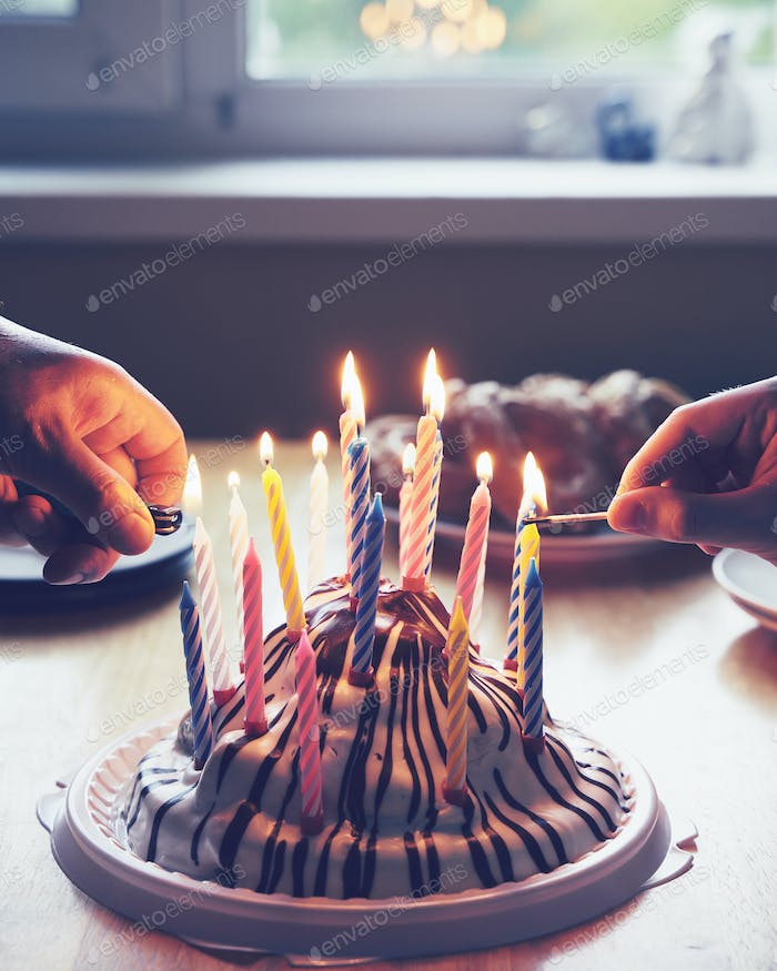Colorful birthday cake with with hands burning nineteen candles home party
