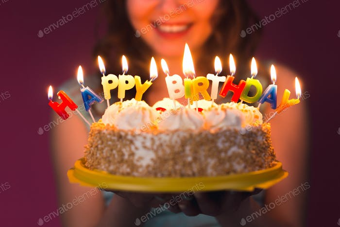 Hands of young woman holding birthday cake selective focus