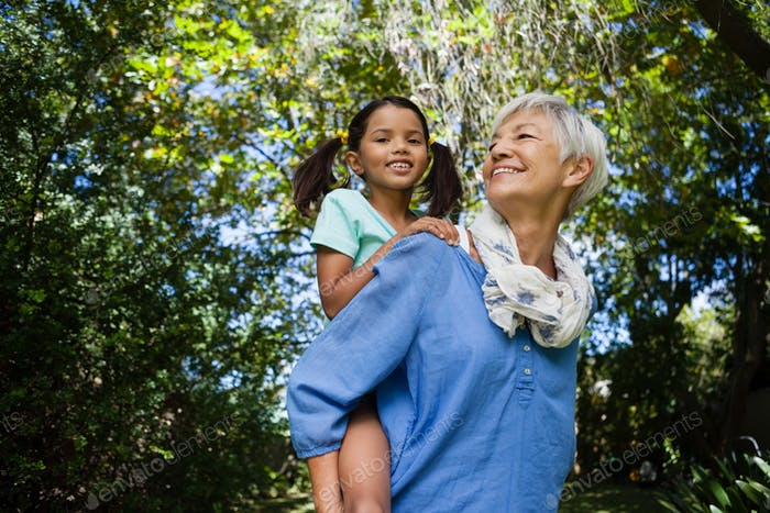 Low angle view of smiling grandmother giving piggyback to granddaughter against trees