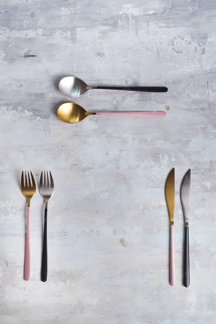 Set of stylish black and pink cutlery on stone background. Fashionable and luxury eating. Flat-lay