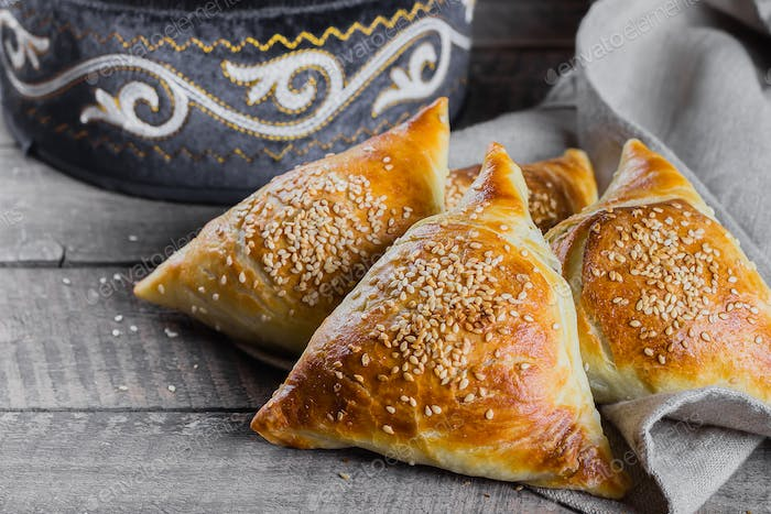 Delicious samsa with meat on wooden table, top view. East Asian Dish. Ramadan food