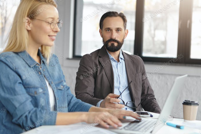 Serious bearded man in jacket and shirt controls female`s work, collaborate together, work on common