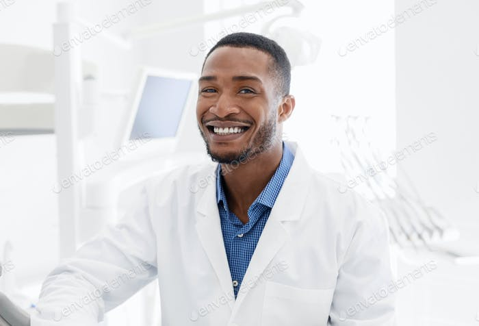 Handsome black dentist smiling over modern dental clinic background