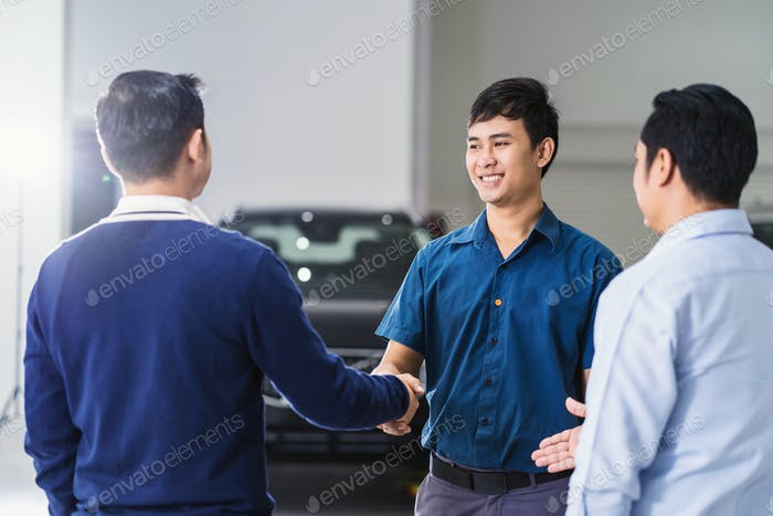 Asian Mechanic handshake with the customer and leader in maintenance service