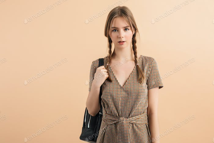 Young beautiful lady with braids in tweed dress holding black backpack dreamily looking in camera