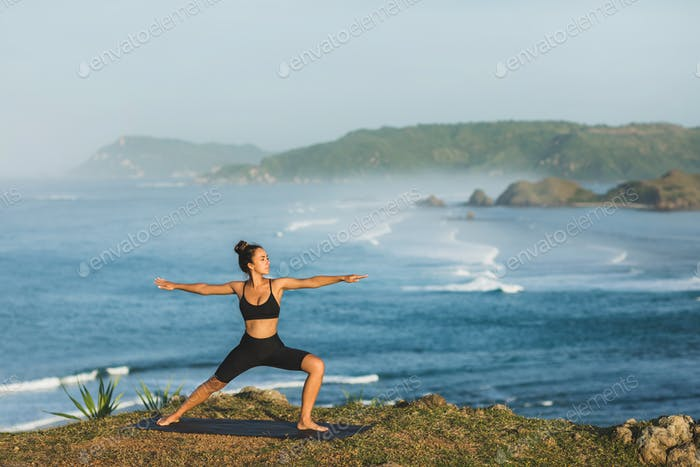 Woman practicing yoga outdoors with amazing ocean and mountain view in morning