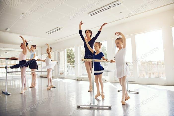 Woman teaching little ballerinas in ballet class