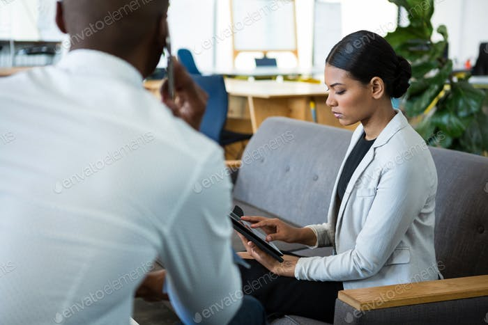 Businesswoman using digital tablet while a colleague talking on mobile phone