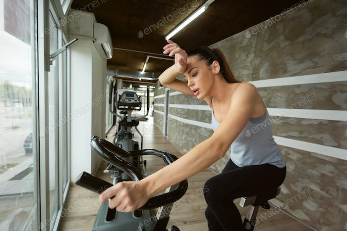 Young beautiful woman doing indoor biking exercise