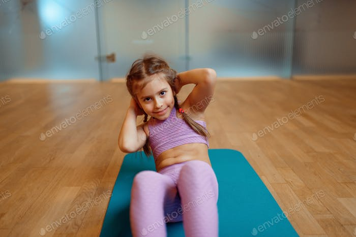 Little girl doing press exercise on mat in gym