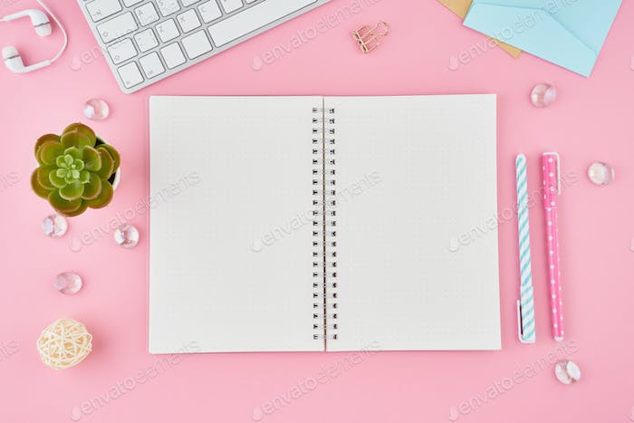 Blank notepad page in bullet journal on bright pink office desktop