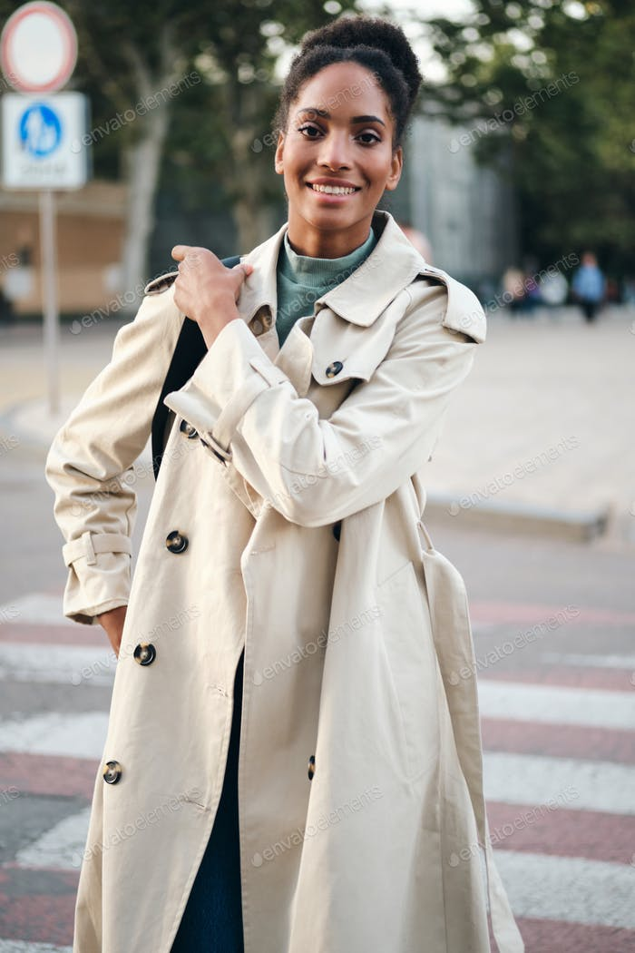 Smiling African American girl in stylish trench coat looking in camera walking down the street