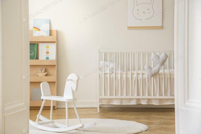 Open door to scandinavian kid's bedroom with white rocking horse