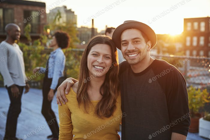 Young adult couple embracing at a rooftop party