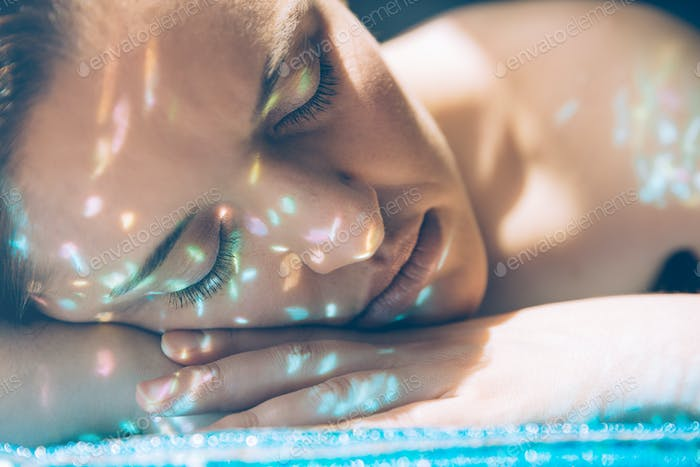 Woman face over hands with sparkles in skin