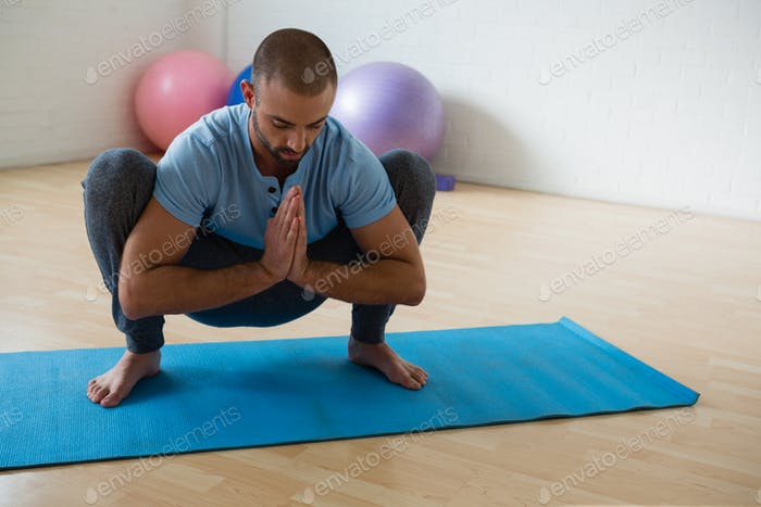 Yoga instructor practicing garland pose in club