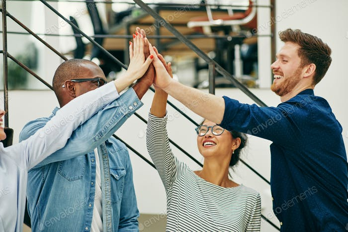 Diverse young businesspeople celebrating with high fives in an office