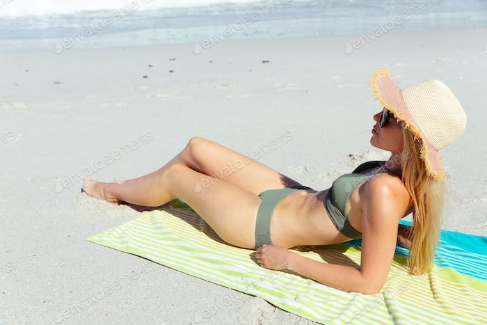 Woman laying on the towel at the beach