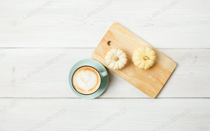 Pumpkin spice latte. Coffee top view on white wood background