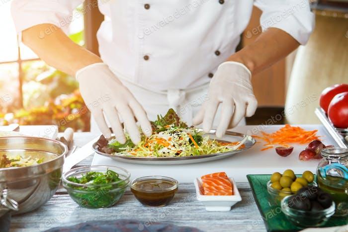 Man's hands prepare salad.