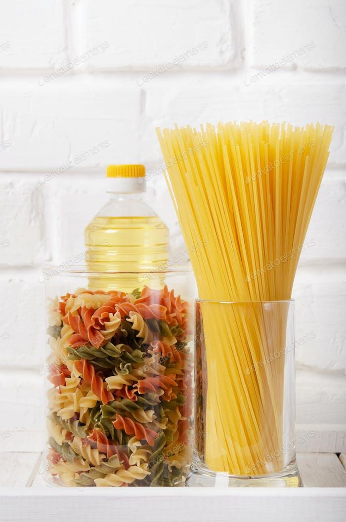 Rohpasta in Gläsern und Speiseöl auf Speisekammer shlelf