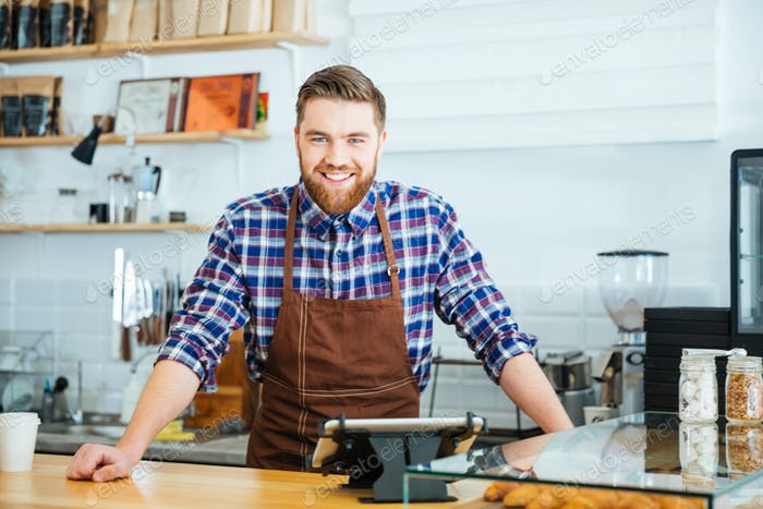 Happy handsome barista in checkered shirt and brown apron