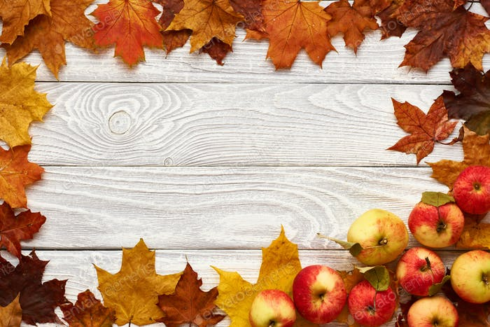 Autumn leaves and apples over old wooden background