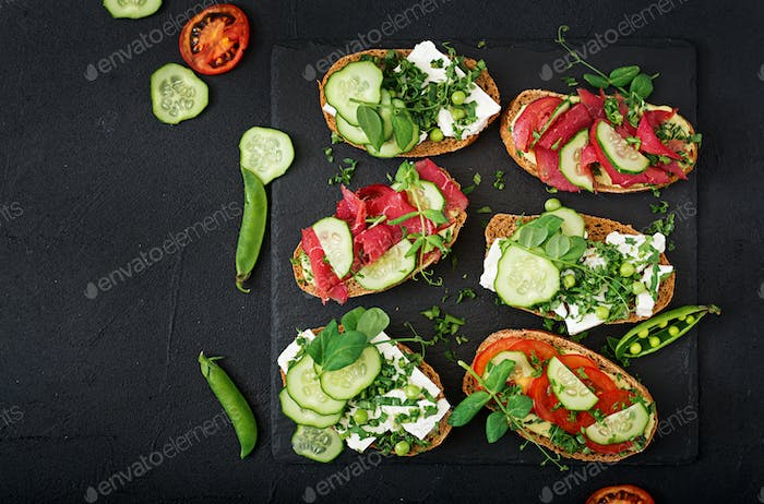 Variety of healthy sandwiches on a dark background in a rustic style. Top view. Flat lay