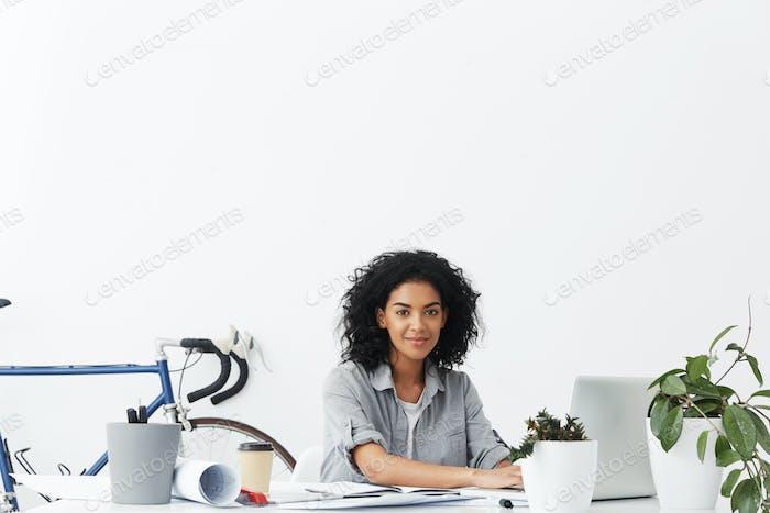 Müde, aber fröhliche, junge, dunkelhäutige, selbständige Architektin, die vor einem offenen Laptop sitzt