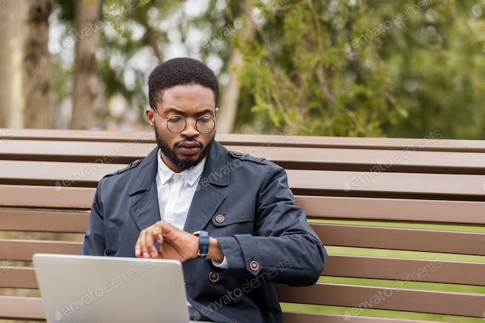Freelance man working on laptop outdoors and checking time