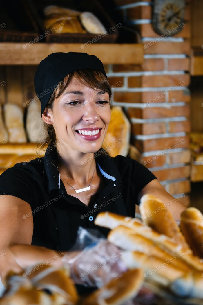 Female Shop Assistant Arrange Pastries In Bakery Shop