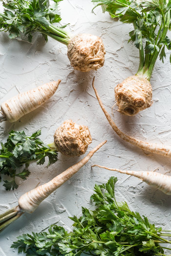 Celery roots and parsley with leaves on a white table