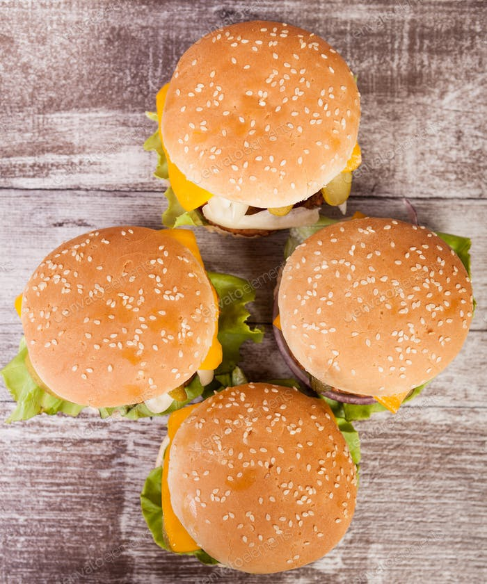 Delicious fresh home made burgers on wooden plate