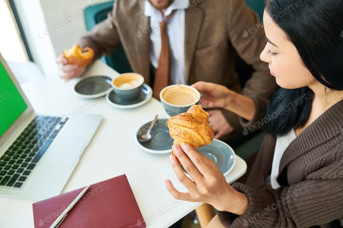 Beautiful Businesswoman Enjoying Coffee with Croissant at Breakf