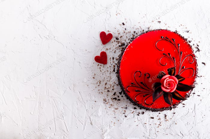 Red Cake with rose, two hearts on white concrete background. Top view. Valentine's Day. Free